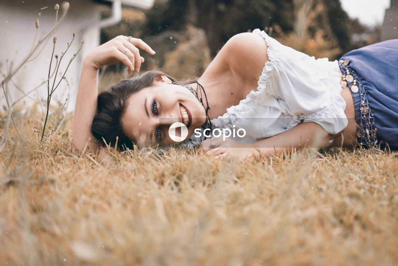 Smiling woman lying on dried glass