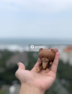 Brown bear figurine on persons hand