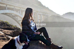 Woman in black and white floral long sleeve shirt and black pants sitting beside black and