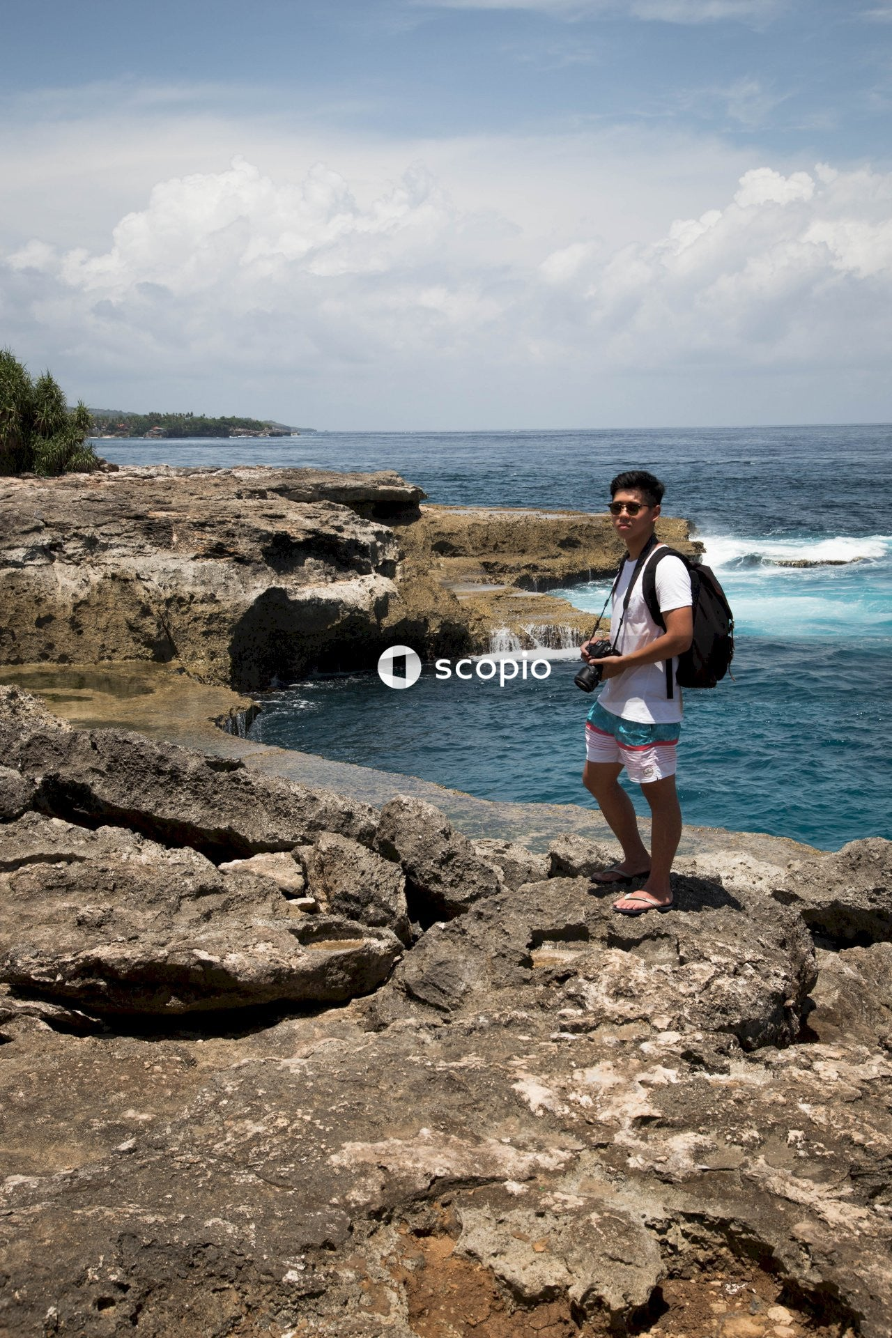 Man standing on rock formation while holding dslr camera