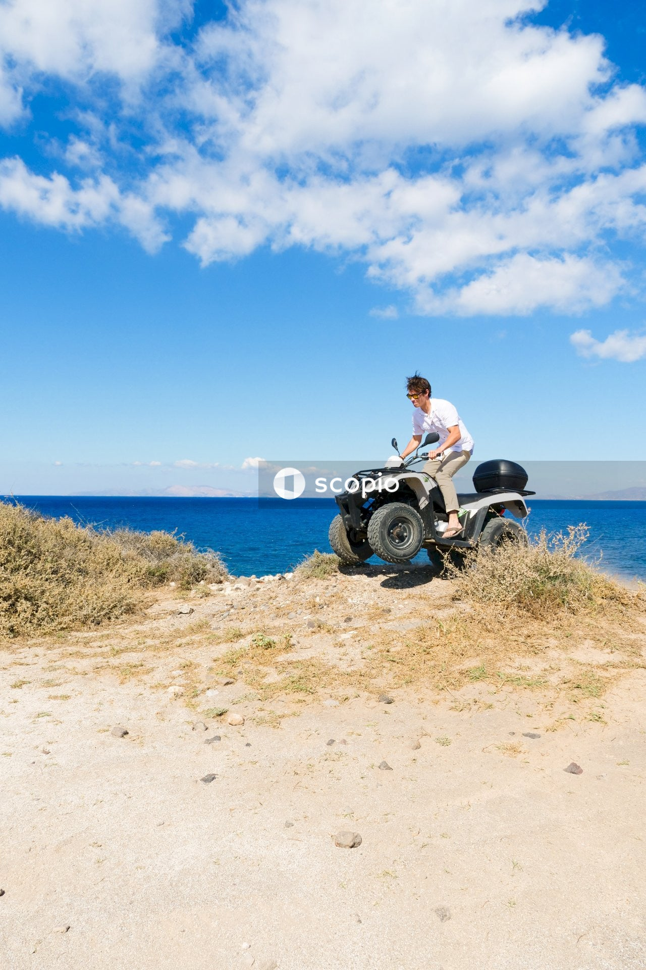 Man in white shirt and black pants sitting on black motorcycle near sea