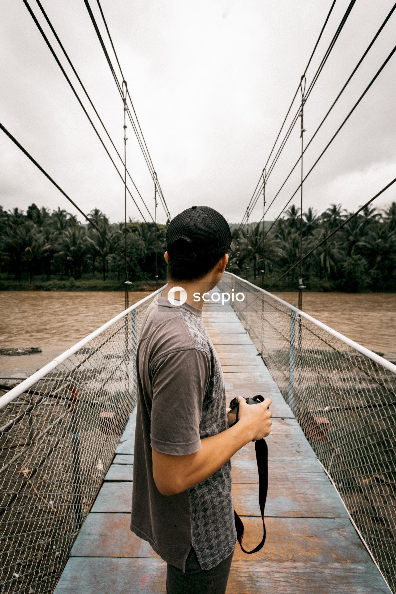 Man in grey t-shirt and black cap standing on bridge