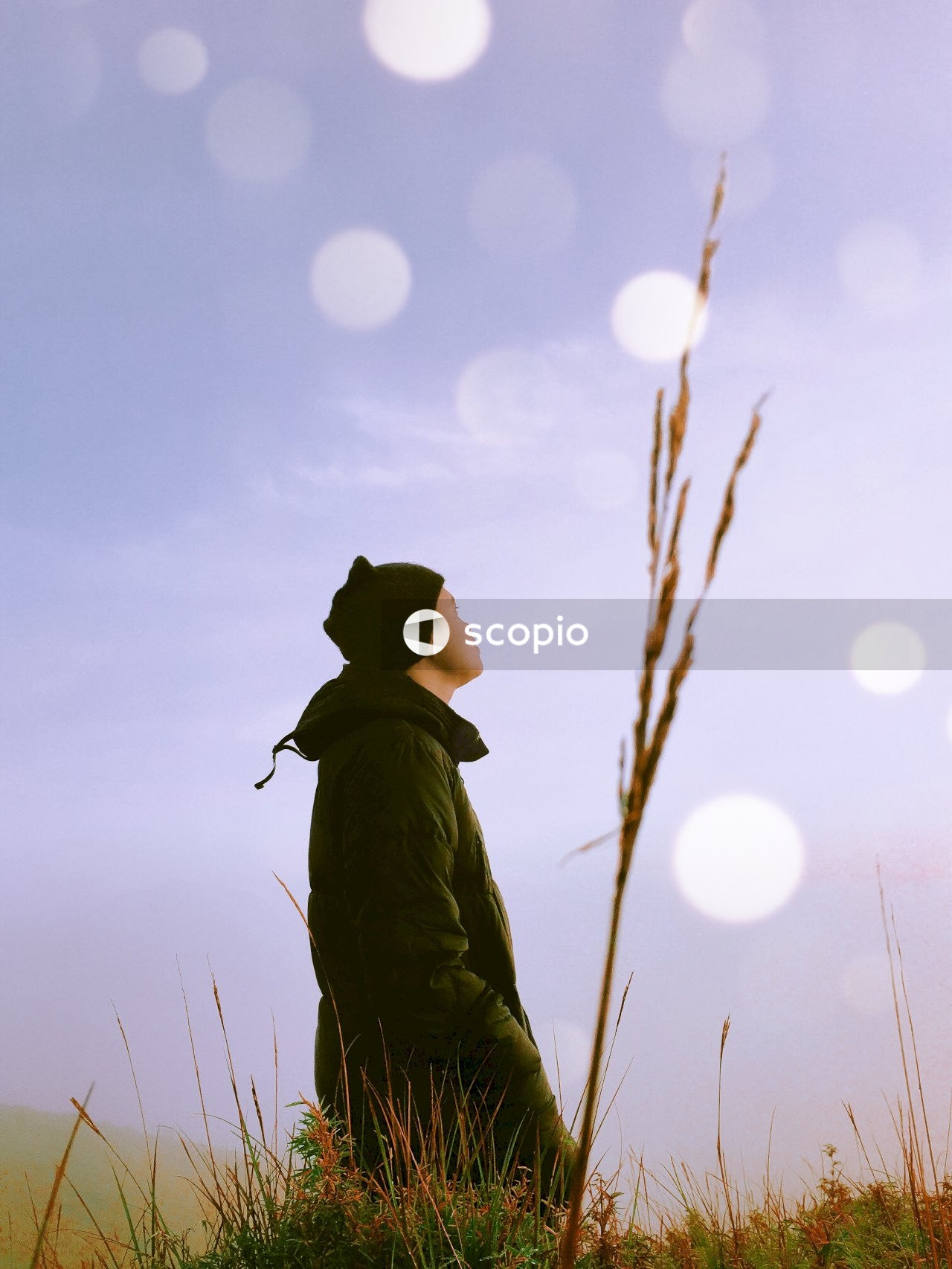 Silhouette of a person wearing black hat and jacket during sunset