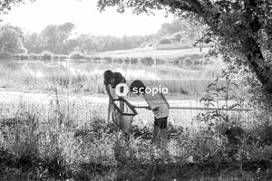 Grayscale photography of man and boy near tree