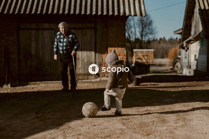 Toddler plays soccer with elderly man