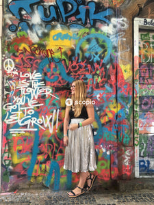 Woman in white and black stripe dress standing in front of graffiti wall