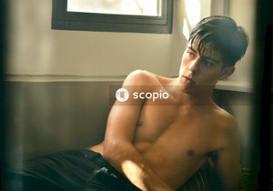 Topless man sitting on black bed