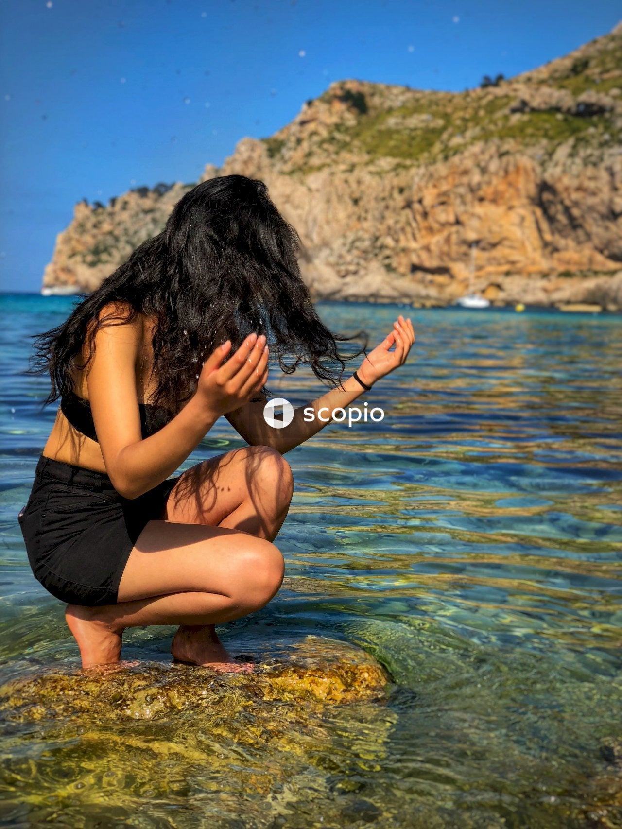 Woman in black shorts sitting on rock in water