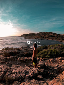 Man in black shorts standing on rocky shore