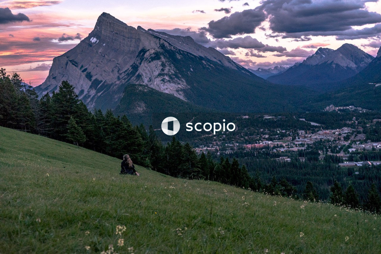 Woman sitting on grass front of mountain