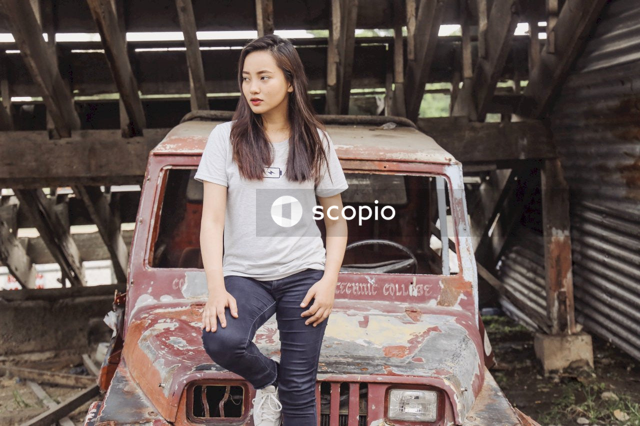 Woman in white shirt and blue denim jeans standing on red car