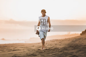 Man in white and black nike tank top running on brown sand
