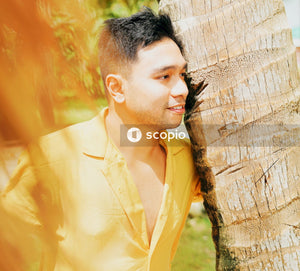 Man in yellow button up shirt leaning on brown tree trunk