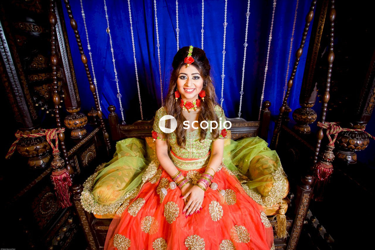 Woman in red and gold sari sitting on green sofa chair