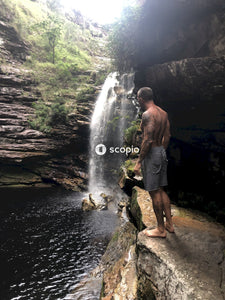 Man standing on cliff beside waterfalls