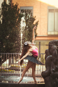Girl in pink tank top and black skirt standing on black rock with water fountain