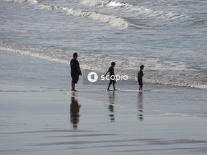 2 men and woman walking on beach