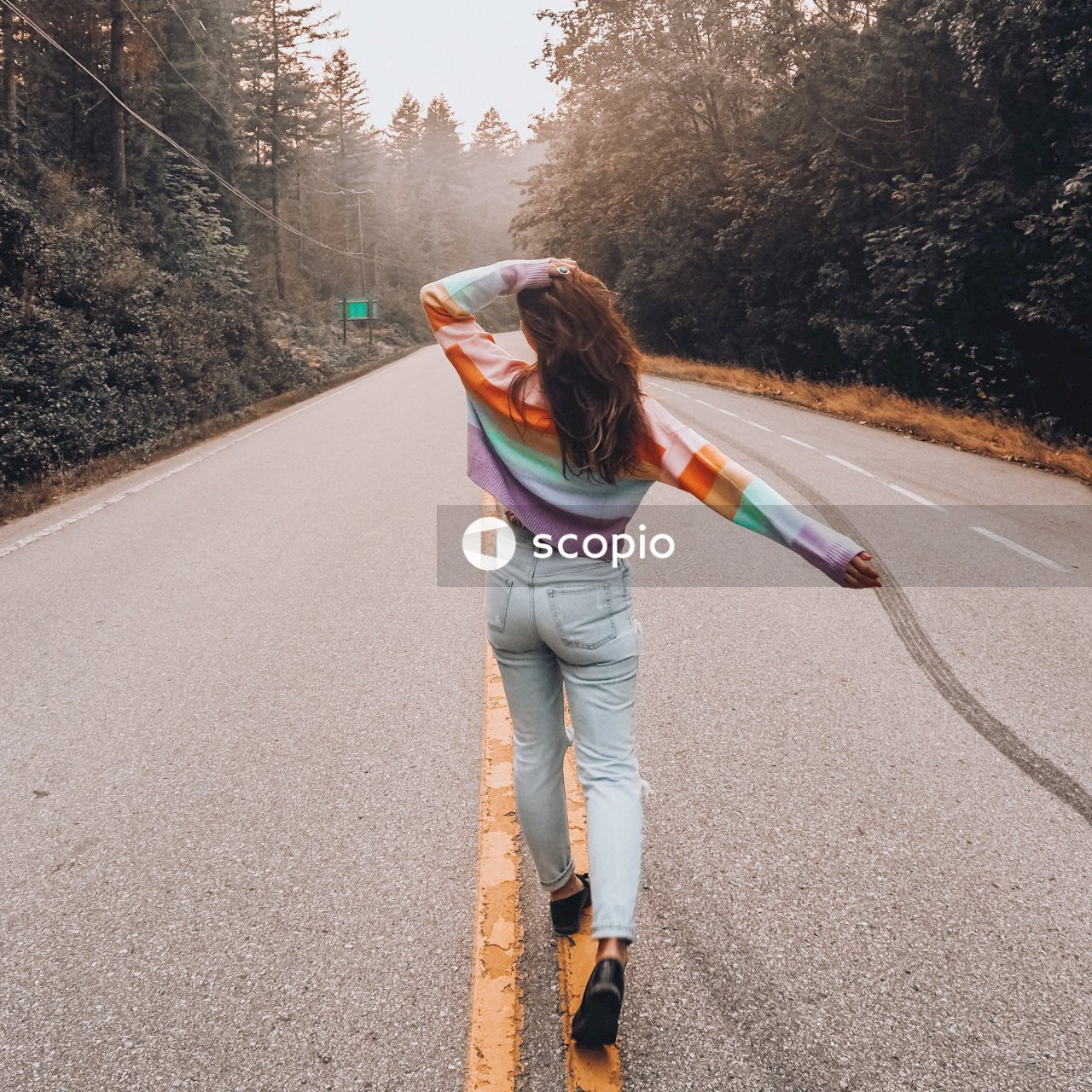Woman in gray jacket and white pants walking on gray asphalt road