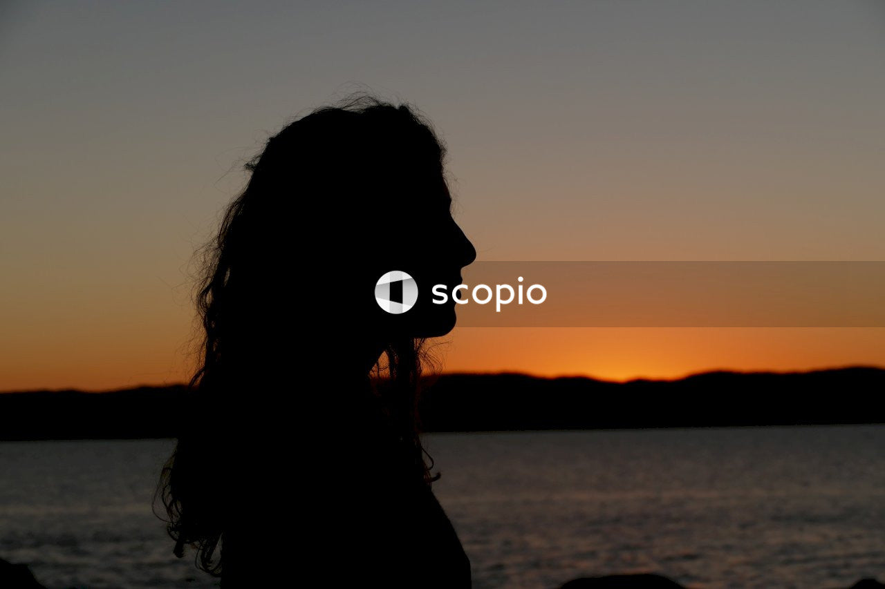 Silhouette of woman near body of water during sunset