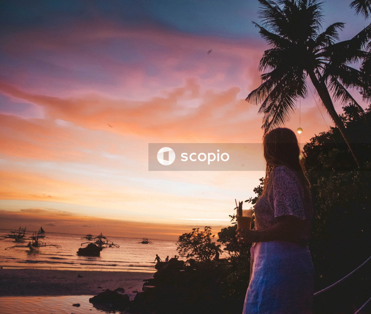 Woman in brown and white floral dress standing on beach during sunset