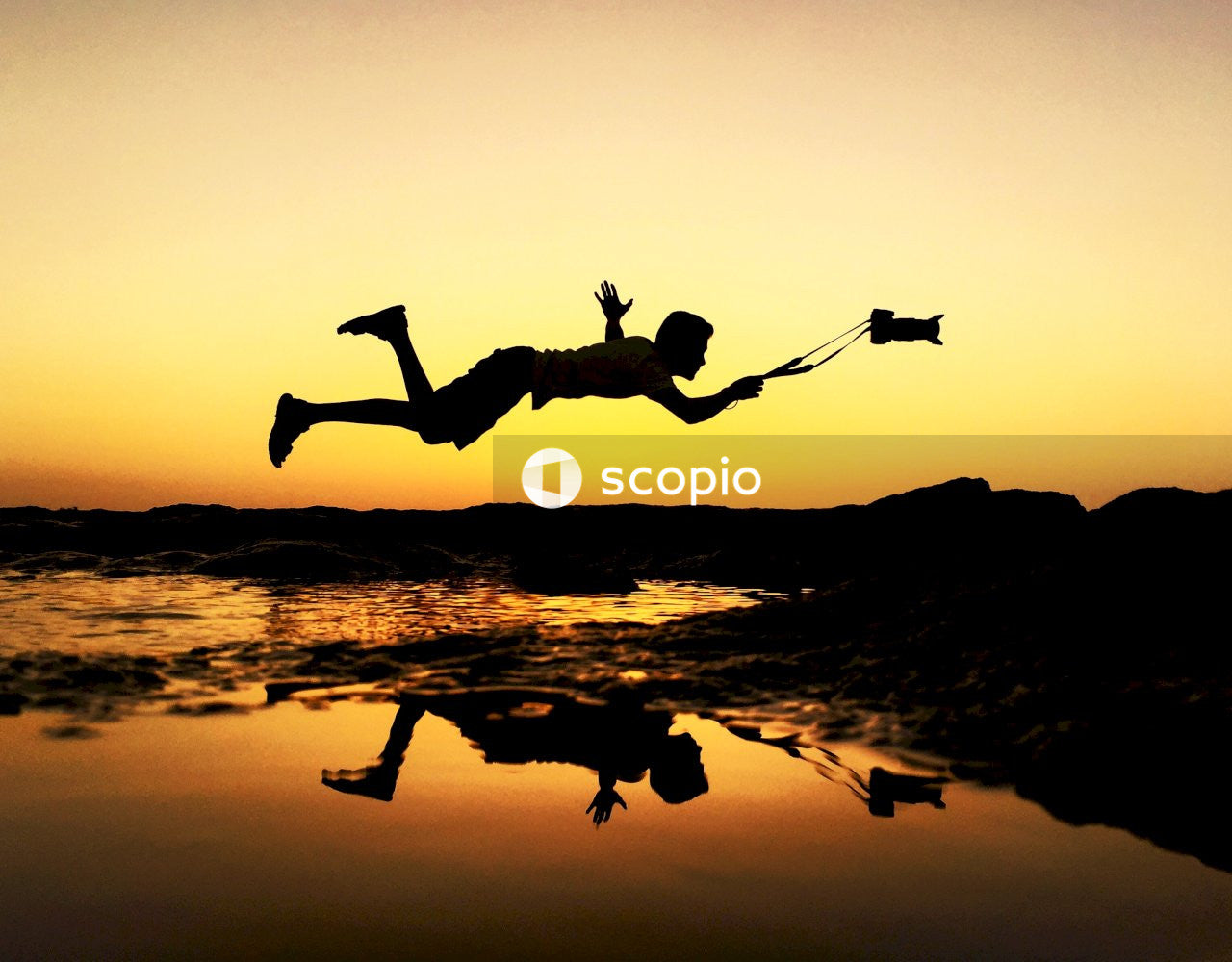 Silhouette of 2 person jumping on water during sunset