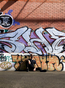 Man in black shirt sitting and leaning on wall with graffiti