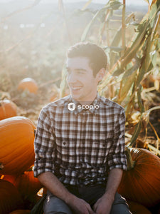 Man in black and white plaid button up shirt sitting on pumpkin field
