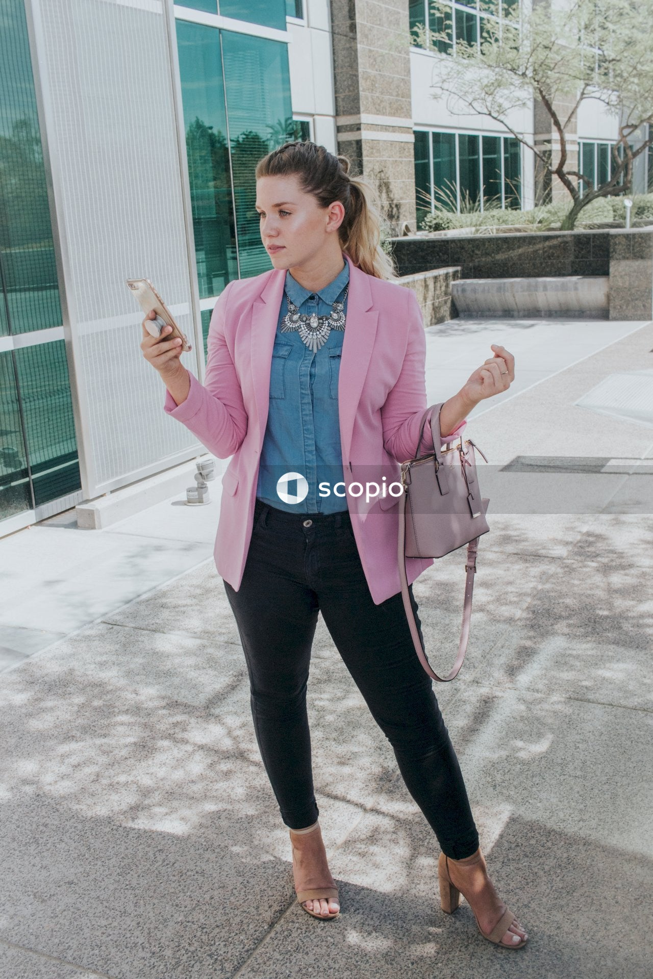 Woman in pink blazer and black pants standing on gray concrete floor