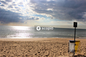 White and blue beach chair on brown sand near body of water
