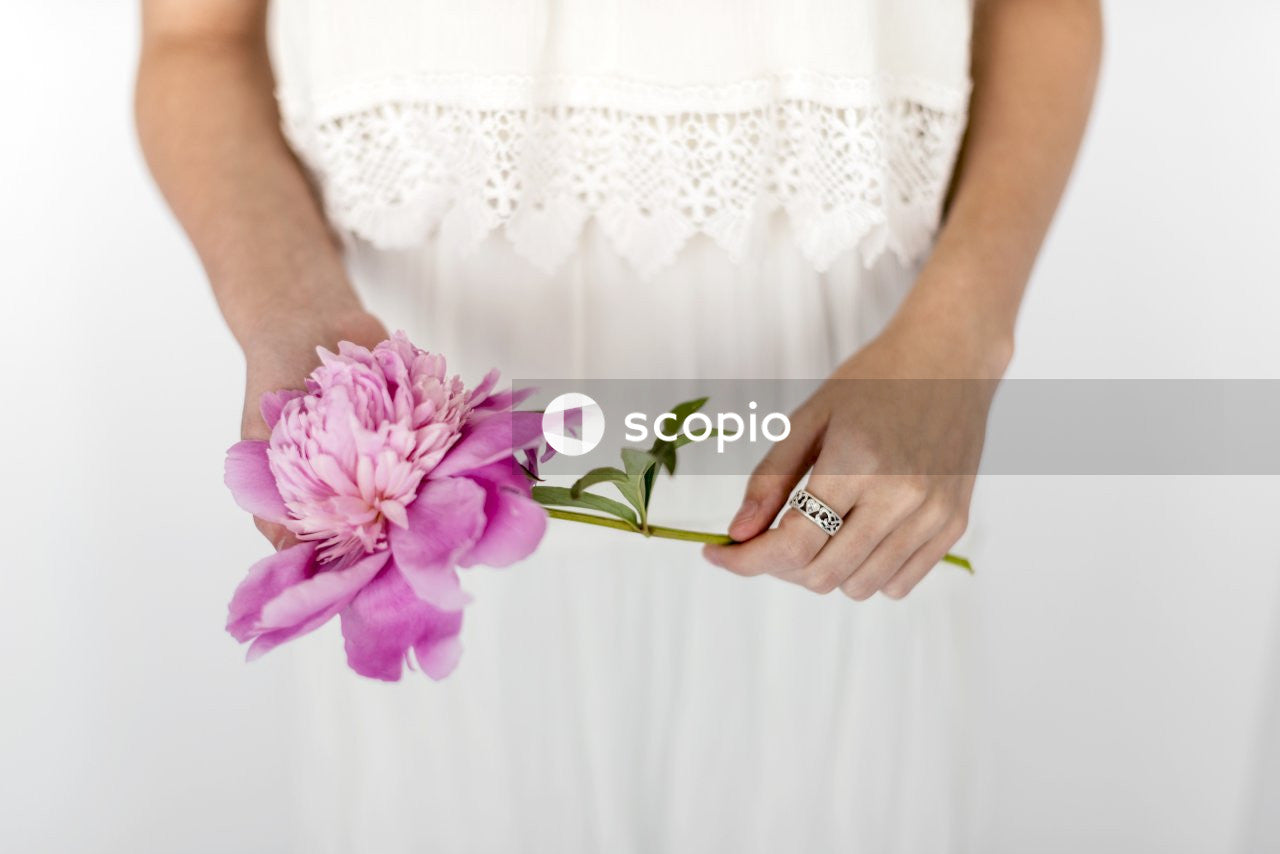 Woman in white lace dress holding pink flower