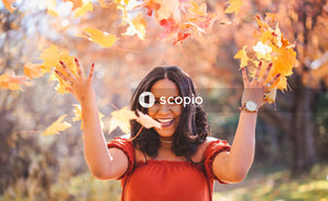 Woman smiling and throwing yellow leaves in the air