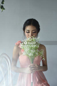 Woman wearing pink dress holding white bouquet
