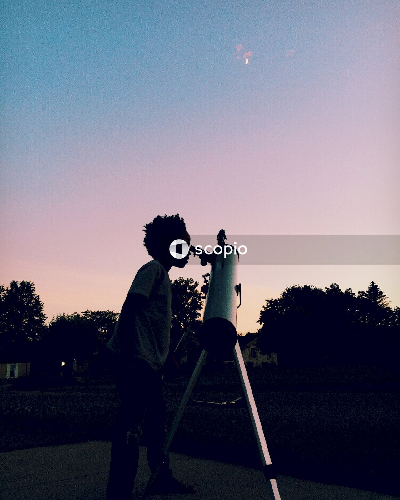Boy standing beside telescope