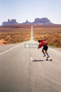 Man skateboarding on long road