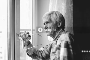 Greyscale photography of man beside window