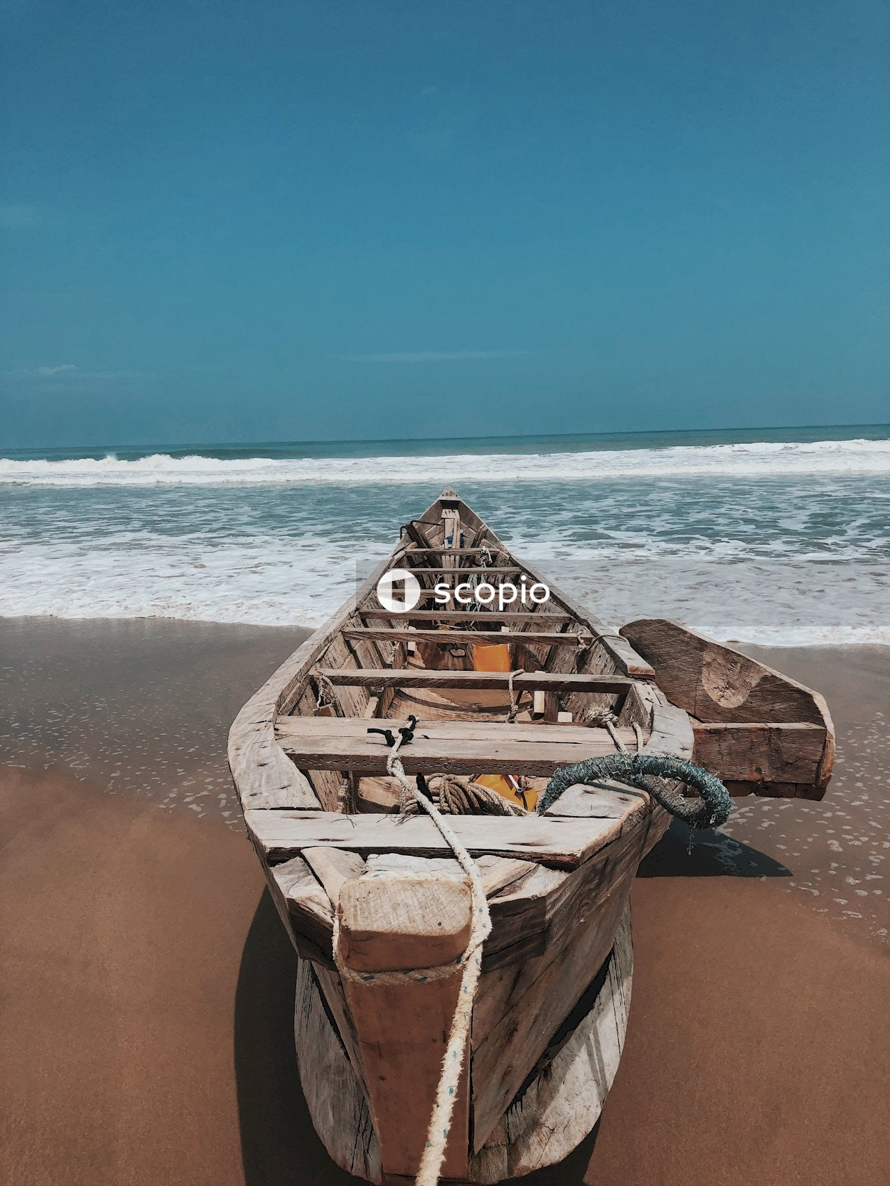 Brown wooden boat on brown sand near body of water