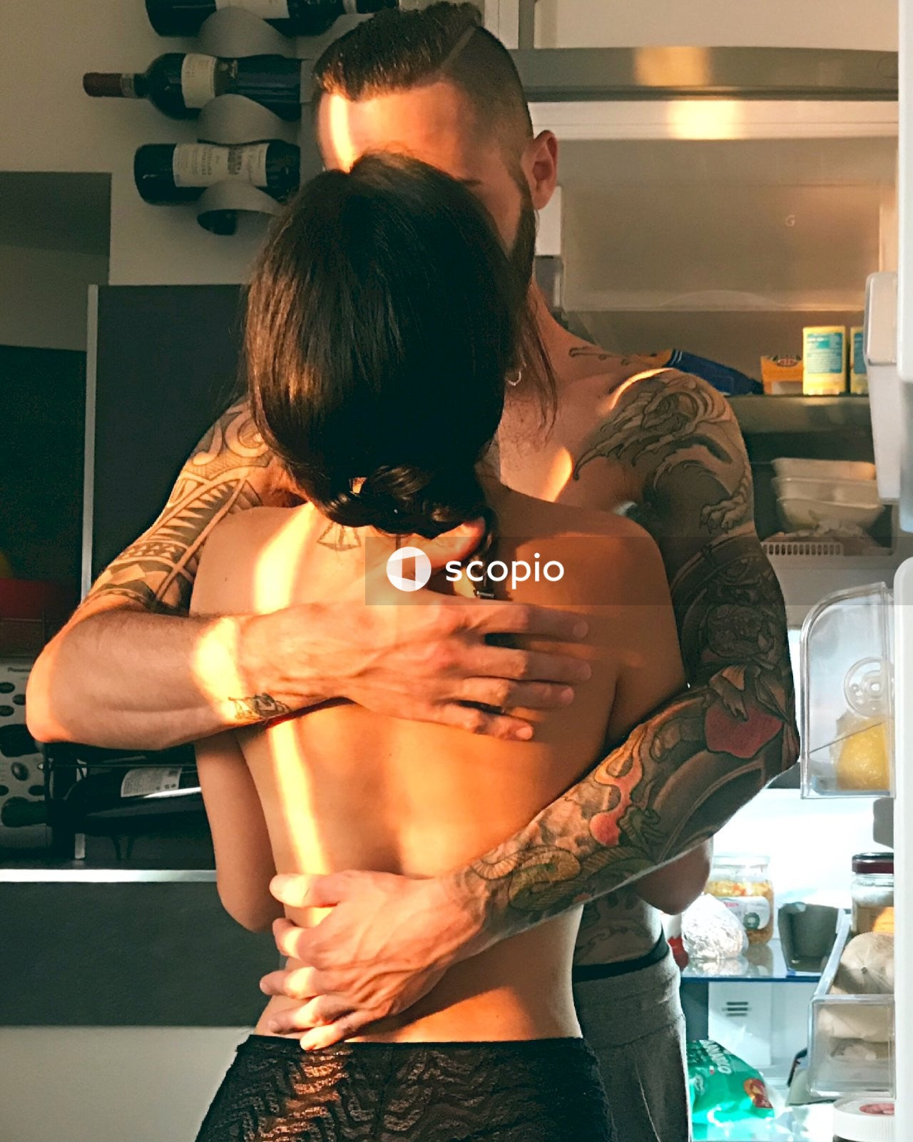 Topless man and woman hugging while facing each other