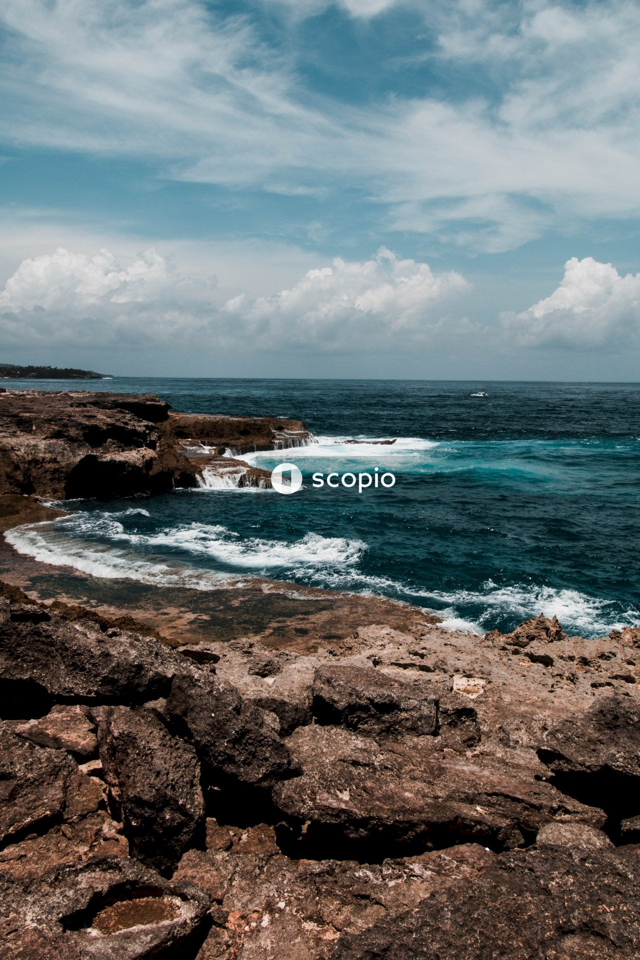 Ocean waves crashing on brown rocky shore under blue and white cloudy sky