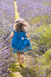 Backside of young girl in blue dress running barefoot in lavender flower field during daytime