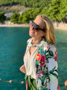 Woman in white red and black floral shirt wearing black sunglasses standing near body of water