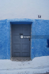 Blue wooden door on blue concrete wall