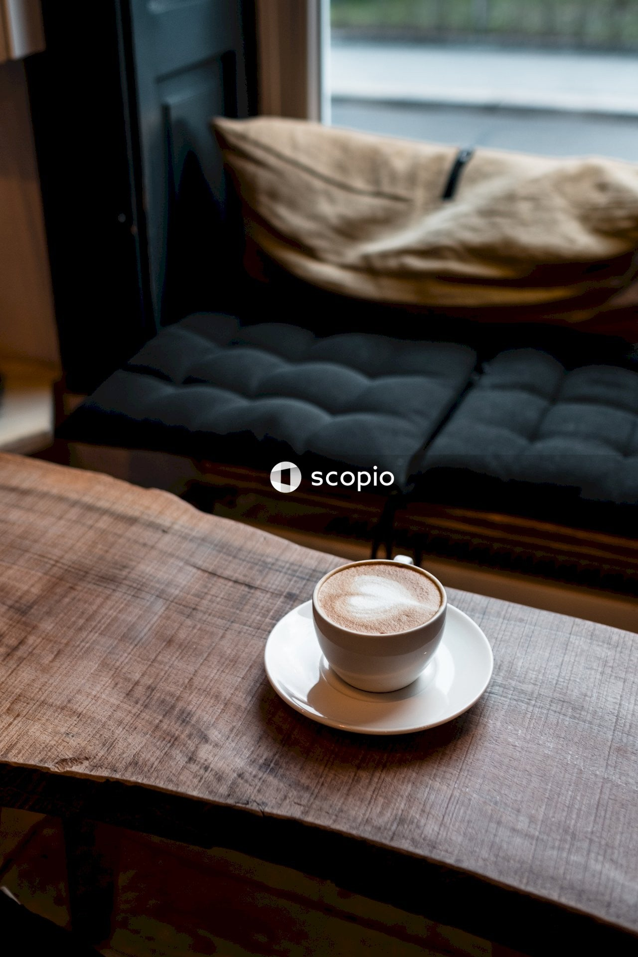White ceramic cup on white ceramic saucer on brown wooden table