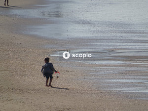 Boy in black t-shirt and black shorts sitting on brown sand beach