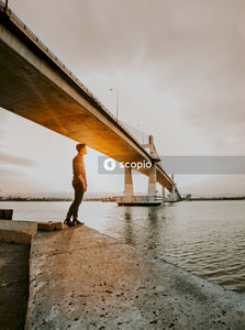 Woman in black jacket and black pants standing on concrete dock