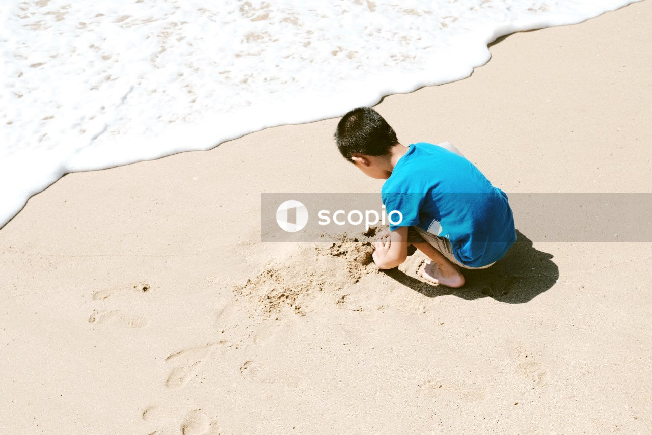 Young boy in blue T-shirt playing with sand near the ocean