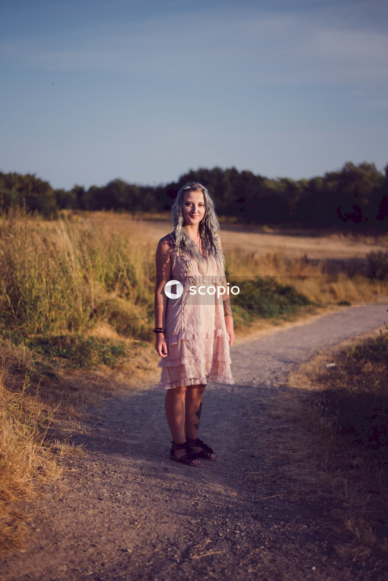 Woman in brown dress standing on dirt road