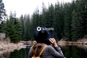 Woman in black hat and black jacket standing near lake