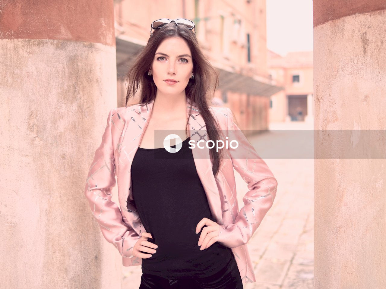 Woman in black tank top and pink blazer standing beside brown concrete wall