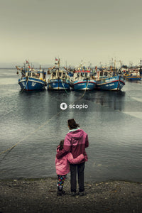 A woman and a little girls standing by the shore looking at boats