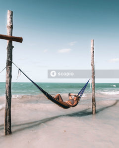 Woman lying on brown hammock on beach